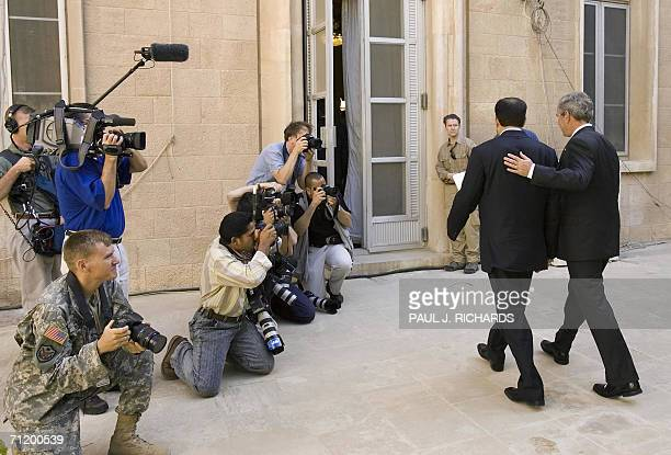 US President George W Bush and Iraqi Prime Minister Nouri alMaliki Baghdad walk in a courtyard past the media 13 June 2006 inside the US Embassy in...