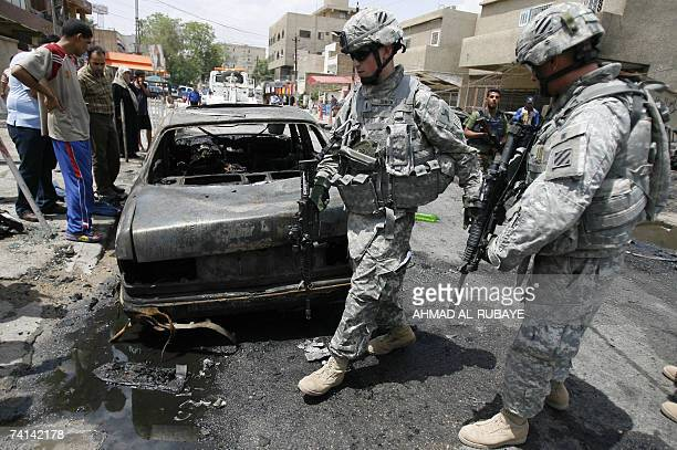 US soldiers and Iraqi civilians look at a burnedout car at the site of a car bomb in the Karrada district near Baghdad city center 14 May 2007 Three...