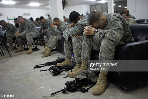 US soldiers hold their heads in prayer during a service held on a US Army forward operating base on the outskirts of Baghdad 28 January 2007 At least...