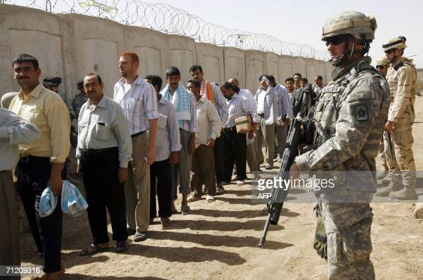 US soldiers stand on guard at the Abu Ghraib prison shortly before prisoners are released as another batch of prisoners were freed under a national...