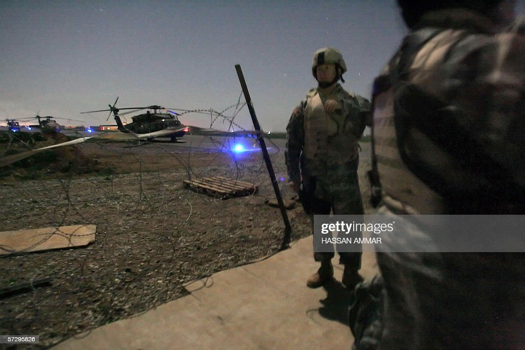 US soldiers wait in line at a helipad to : News Photo