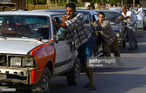 Baghdad Iraq––Ahmed Waleed Ahmed 26 catches a bite for breakfast while inching his car forward in an immense line toward his turn to buy gas he needs...
