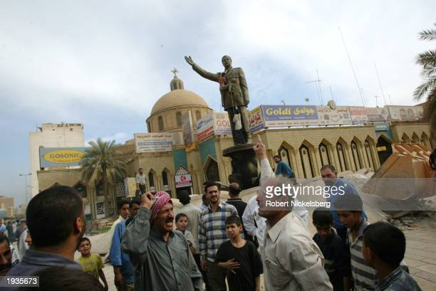 Baghdad residents shout antiSaddam slogans April 12 2003 in front of a downtown Rashid Street monument to the former president in Baghdad Iraq as...