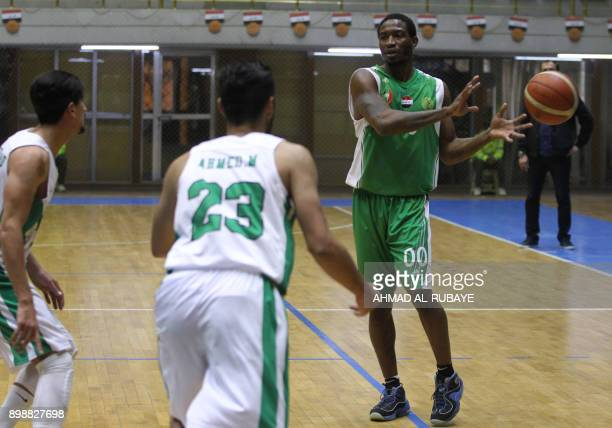 Baghdad's Oil Club guard DeMario Mayfield receives the ball during a basketball match against Iraq's Airline Club in Baghdad on December 7 2017...