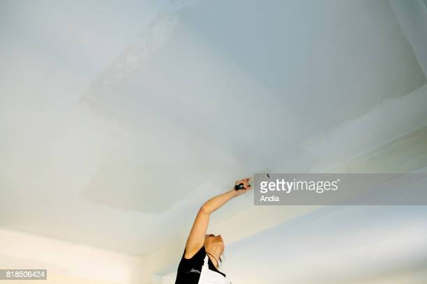 Craftswoman painter interior designor working at a client's place Painting the ceiling with a paint roller