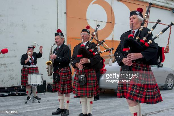 A bagpipe band is playing for a cruise ship in the port of Dunedin on the South Island in New Zealand
