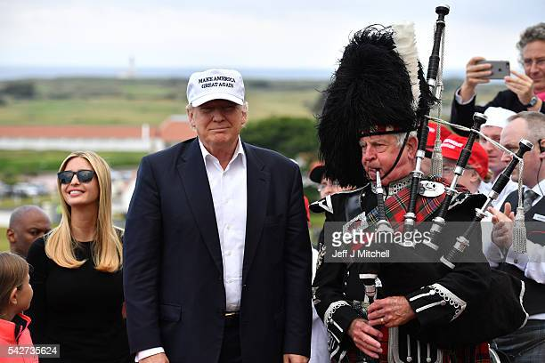 A bagpipe player wears traditional dress next to Presumptive Republican nominee for US president Donald Trump surrounded by his family with his...