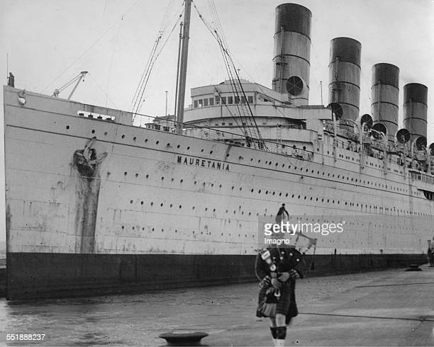 A bagpiper greeted the ocean liner RMS Mauretania on his future last anchorage in Rosyth 4th July 1935 Photograph