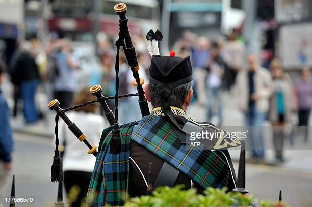 A bagpiper in traditional regalia plays for members of the public on a street in Edinburgh on August 21 2013 during the annual Festival Fringe With...