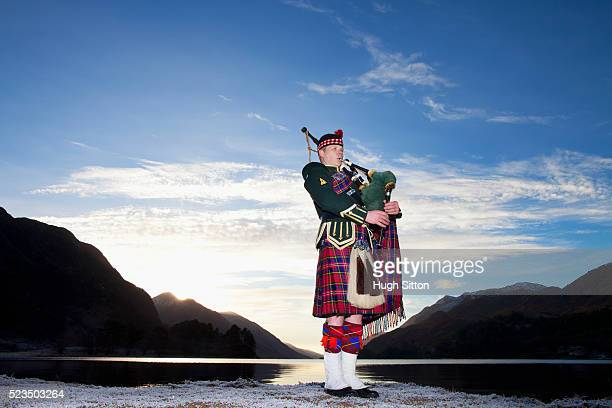 Bagpiper playing bagpipes at Glenfinnan, next to Loch Shiel. West Coast Scotland