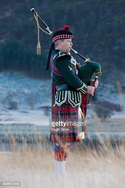 bagpiper playing bagpipes at glenfinnan, next to loch shiel. west coast scotland - hugh sitton stock pictures, royalty-free photos & images