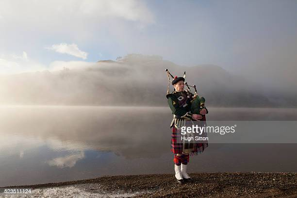 Bagpiper playing bagpipes, standing next to Scottish Loch. West Coast Scotland