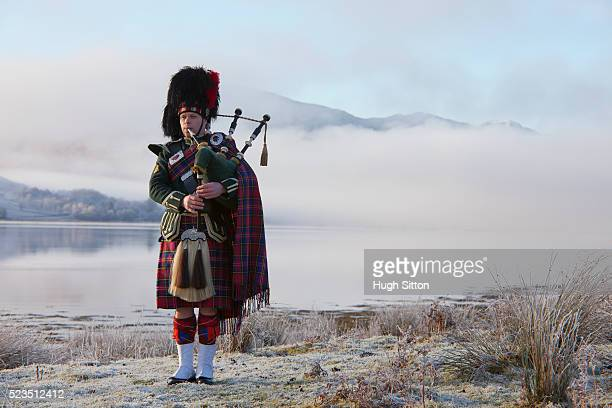 bagpiper playing bagpipes, standing next to scottish loch. west coast scotland - hugh sitton stock pictures, royalty-free photos & images