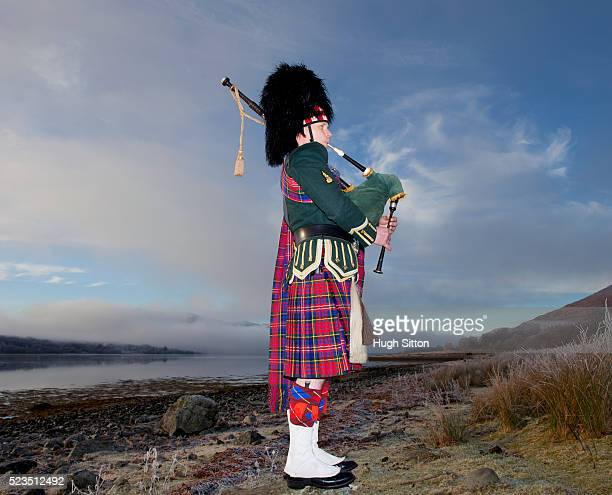 bagpiper playing bagpipes, standing next to scottish loch. west coast scotland - hugh sitton stockfoto's en -beelden