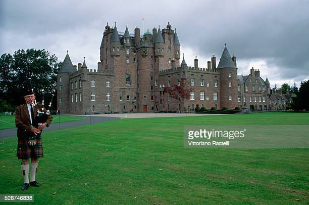 A bagpiper plays outside Glamis Castle family home of the Queen Mother in Tayside Scotland