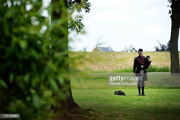 A bagpiper poses with his instrument during the BagOpen International Pipeband Competition of the Scottish Festival in Xanten western Germany on 16...