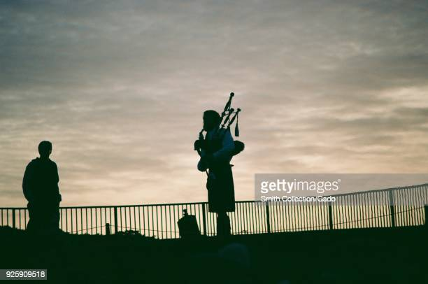 Bagpiper wearing traditional Scottish kilt is visible in silhouette against a sunset at the Ritz Carlton luxury hotel in Half Moon Bay California...