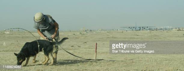 Bagram, Afghanistan-6/2004--Having worked a large mine field with specially trained dogs that have identified particular spots for mines, a de-miner...
