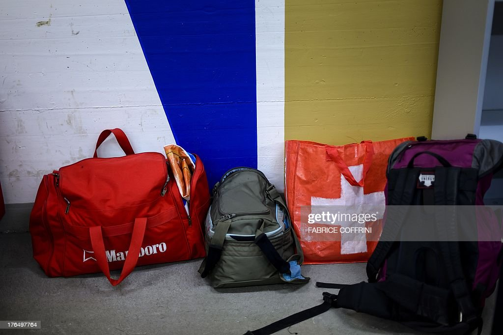 Bags belonging to asylum seekers with one bearing the Swiss national flag are seen in a subterranean shelter used as temporary asylum center on August 14, 2013 in Kestenholz. Police proceeded this week to remove 10 asylum seekers who had been camping out for days at the Solothurn train station in northwestern Switzerland in protest against their living conditions in a subterranean bunker in Kestenholz they described as 'unworthy of a human being'. Switzerland, which prides itself on its humanitarian principles, is facing a barrage of criticism over its treatment of asylum seekers.