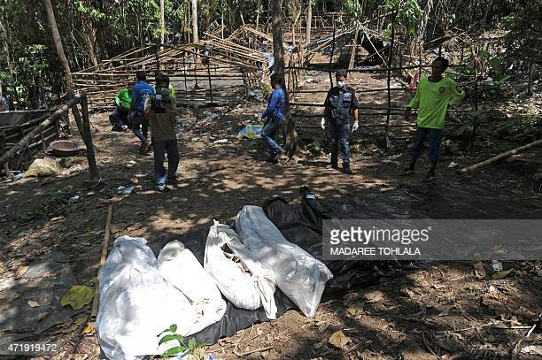 Bags containing skeletons dug out from shallow graves lay on the ground at the site of a mass grave at an abandoned jungle camp in the Sadao district...