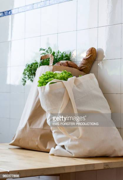 2 bags full of fresh healthy biological food in a kitchen on a table while bright day. - shopping bag stock pictures, royalty-free photos & images