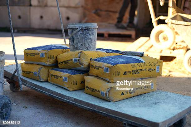Bags of cement sit on a cart at the yard of Gully Concrete supplies in Melbourne Australia on Tuesday Aug 16 2016 Australia's economy is enjoying an...