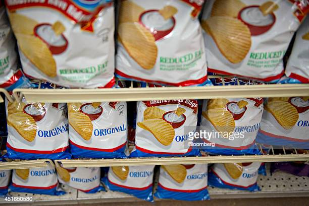 Bags of Frito Lay North America Inc Ruffles brand potato chips sit on display for sale in a supermarket in Princeton Illinois US on Wednesday July 2...