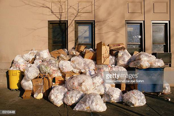 Bags of garbage sitting on side of building
