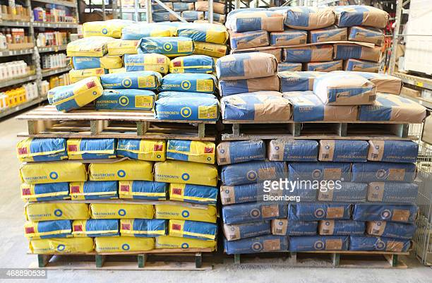 Bags of general purpose right and Mastercrete left building cement manufactured by Lafarge SA sit on pallets inside a BQ home improvement store...