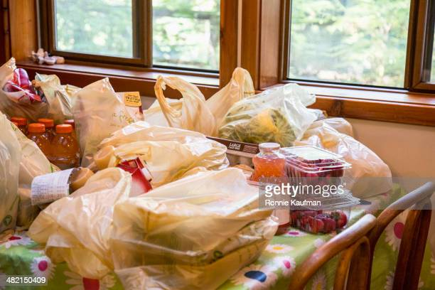 bags of groceries on dining room table - ビニール袋 ストックフォトと画像
