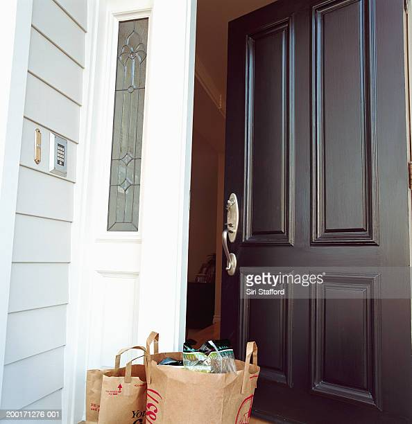 Bags of grocery in front of open door