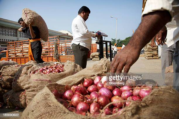 Bags of onions are displayed for sale at a wholesale market in Nashik Maharashtra India on Wednesday Oct 23 2013 Onion prices in India may extend a...