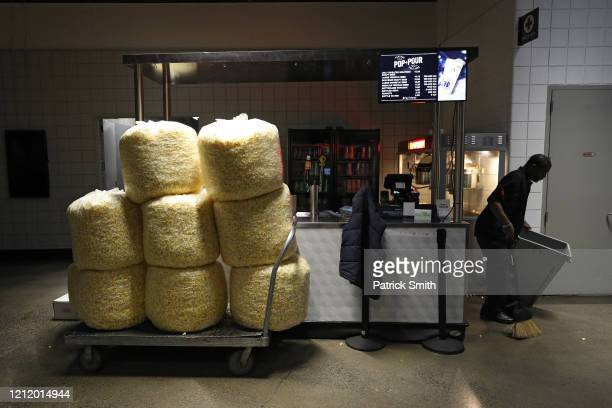 Bags of popcorn rest on a cart as a man cleans behind a vendor kiosk prior to the Detroit Red Wings playing against the Washington Capitals at...