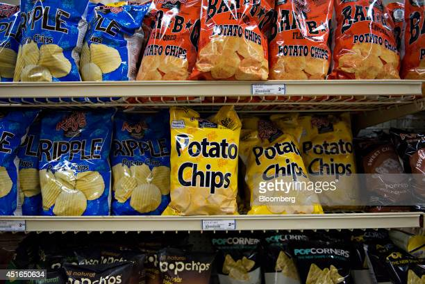 Bags of potato chips sit on display for sale in a supermarket in Princeton Illinois US on Wednesday July 2 2014 Rising prices for beef ice cream and...