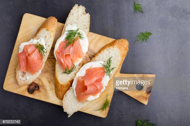baguette slices with cream cheese and smoked salmon - smoked food fotografías e imágenes de stock
