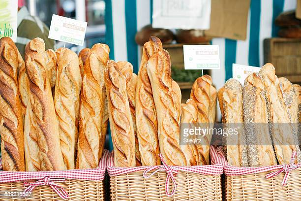 baguettes at the market - baguette stock pictures, royalty-free photos & images