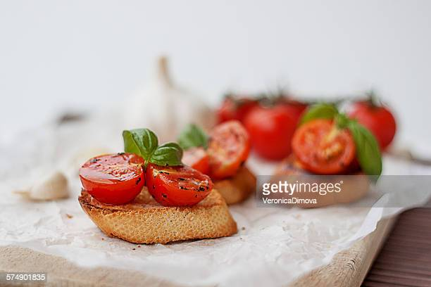 baguettes with cherry tomatoes, basil and garlic - appetizer stock pictures, royalty-free photos & images