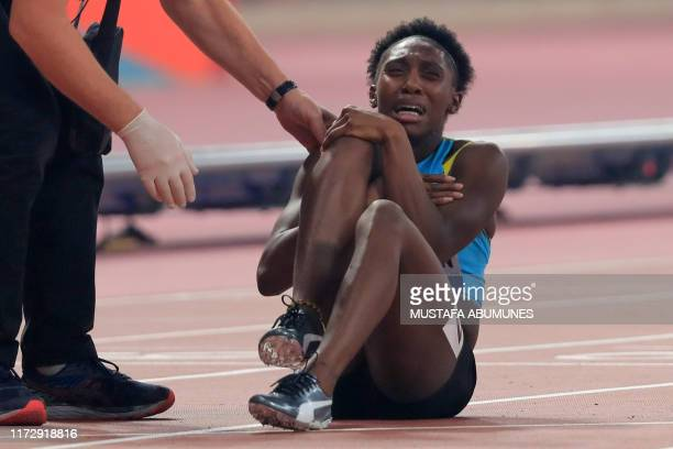 Bahamas' Anthonique Strachan holds her knee at the end of the Women's 200m semifinal at the 2019 IAAF Athletics World Championships at the Khalifa...