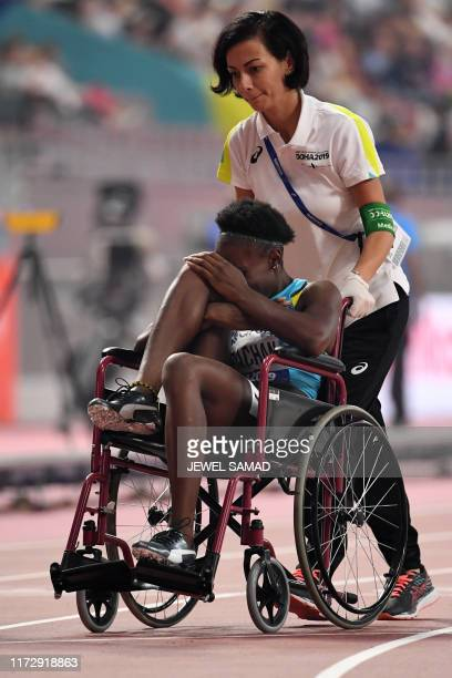 Bahamas' Anthonique Strachan is helped onto a wheelchair after picking up an injury while competing in the Women's 200m semifinal at the 2019 IAAF...