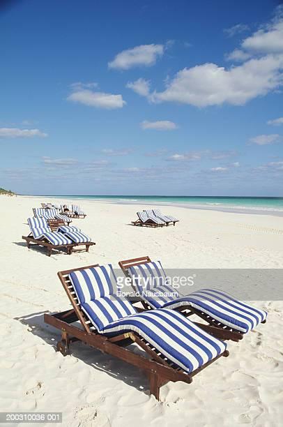 bahamas, harbor island, striped beach chairs on beach - harbor island bahamas stock photos and pictures