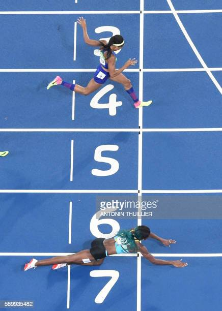 TOPSHOT Bahamas' Shaunae Miller dives to cross the finish line ahead of USA's Chase Kalisz during the Women's 400m Final during the athletics event...