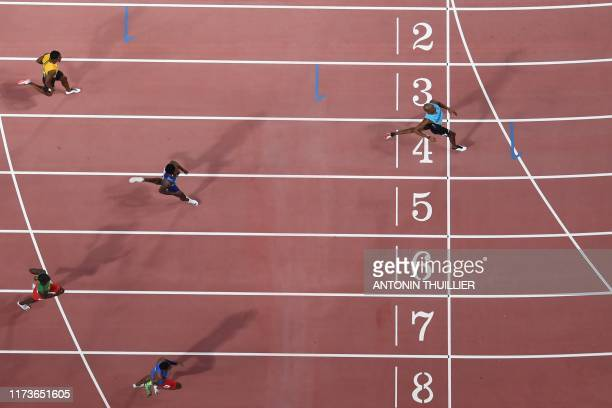 Bahamas' Steven Gardiner leads and crosses the finish line in the Men's 400m final at the 2019 IAAF Athletics World Championships at the Khalifa...
