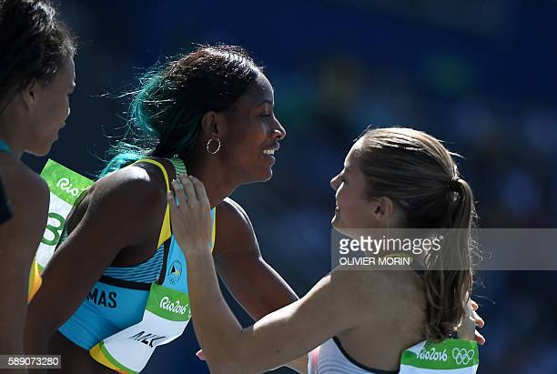 Bahamas's Shaunae Miller is congratulated by Germany's Ruth Sophia Spelmeyer after they competed in the Women's 400m Round 1 during the athletics...