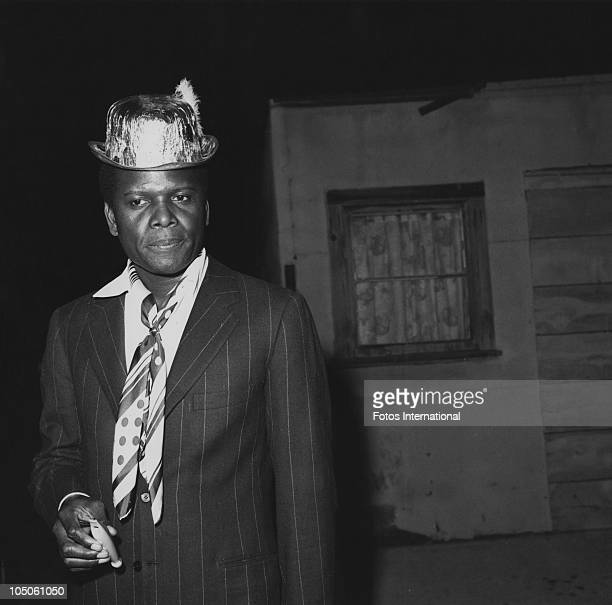 Bahamian American actor Sidney Poitier wearing a foil party hat and holding a whistle at a 'Holiday on Ice' skating revue circa 1968