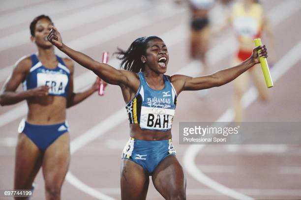 Bahamian track athlete Debbie FergusonMcKenzie raises her arms in the air in celebration as she crosses the finish line in first place for the...