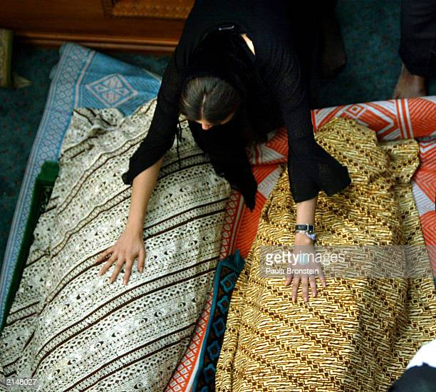 Bahar Niko places her hands on the bodies of her friends Iranian twins Laleh and Ladan Bijani during a memorial service July 9 2003 in Singapore The...