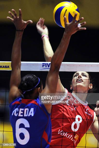 Bahar Toksoy of Turkey spikes the ball beside Peru's Jessenia Uceda during their Pool E second round match at the FIVB 2010 Women's Volleyball World...