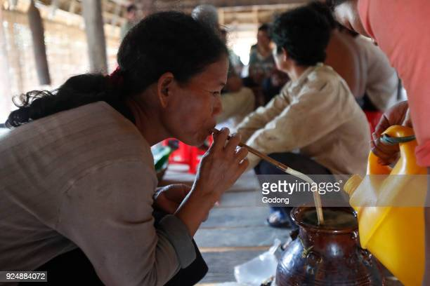 Bahnar ethnic minority people's communal Rong house Woman drinking tarditional rice wine Kon Tum Vietnam