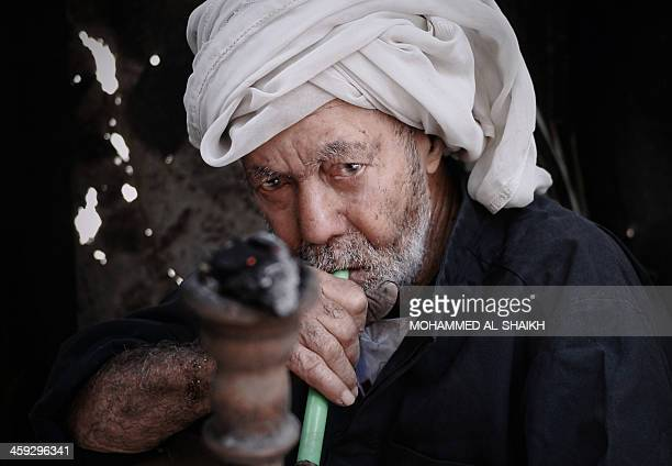 A Bahrain farmer sits smoking a water pipe during a break as he works in his farm in the village of Bori south of Manama on December 25 2013 AFP...