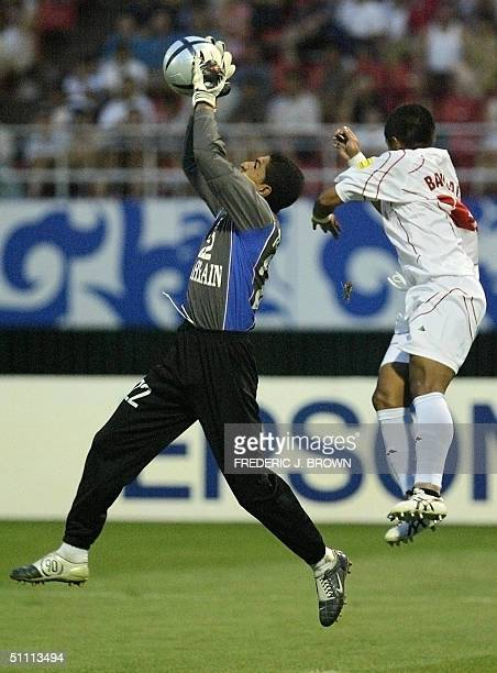 Bahrain goalkeeper Ali Saeed Abdulla collects a cross under pressure from Indonesia's Bambang Pamungkas 25 July 2004 in Jinan during Asian Cup soccer...